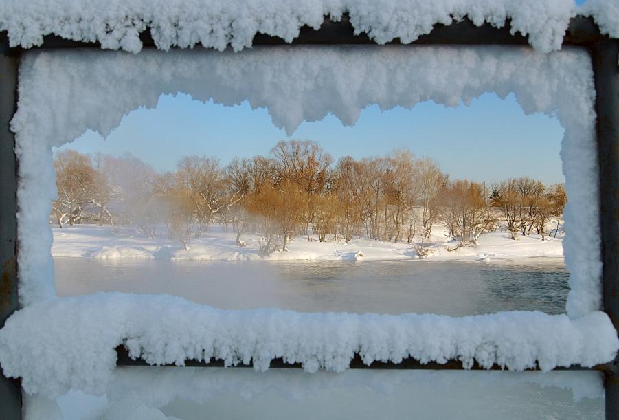 Сквозь заснеженное окно виден зимний пейзаж