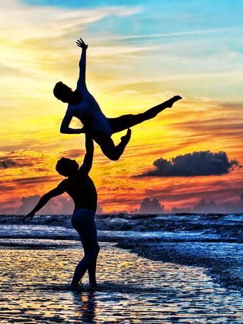 Фото Танцовщик в трико поднимает балерину одной рукой на берегу моря на фоне заката