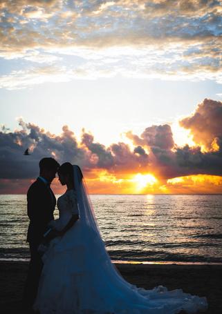 Фото Жених и невеста стоят на берегу моря на закате в трогательной позе, соприкаснувшись лбами