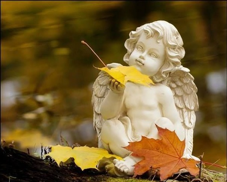 Фото Скульптура ангела с осенним листом в руке