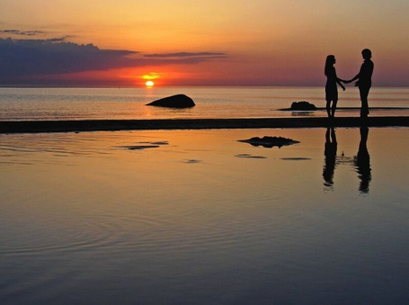 Фото Девушка и парень стоят в морском прибое взявшись за руки на фоне красивого, тонущего в море диска солнца