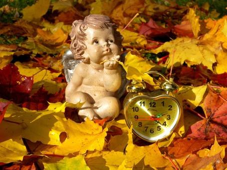 Фото Фигурка ангелочка на осенних листьях посылает воздушный поцелуй, рядом часы сердечком