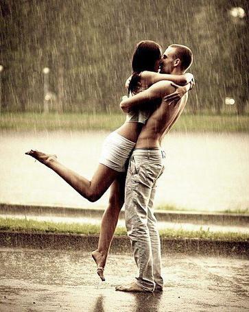 Фото Босоногий парень с голым торсом приподнял за талию и нежно целует изящную босоногую девушку под проливным дождем