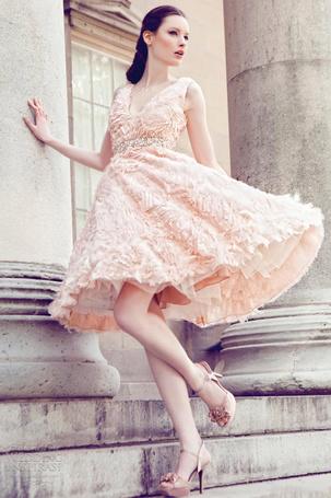 Фото Девушка в нежно-персиковом платье стоит у колонны здания, японская модельер Юми Катсура / Yumi Katsura