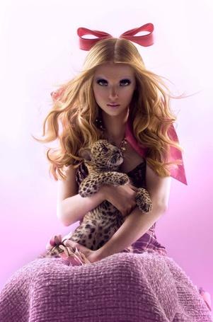 Фото Блондинка в розовом платье и огромном банте сидит и держит маленького леопарда