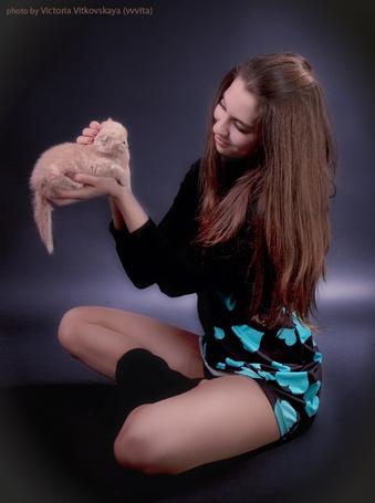 Фото Девушка в коротком платье сидит на полу, держит на ладони рыжего котенка и гладит его с улыбкой на лице. Фотограф Виктория Витковская / Vitkovskaya Victoria/