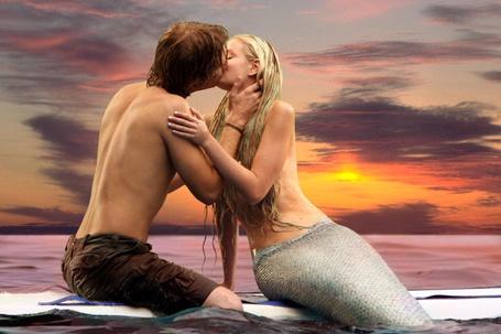 Фото Русалка целует парня на закате солнца в море на доске для серфинга