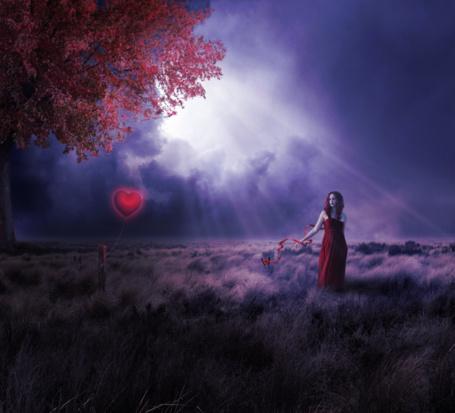 Фото Девушка в красном платье стоит в поле под лучами солнца, рядом столб с привязанным воздушным шаром в виде сердца