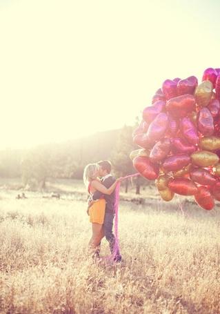 Фото Мужчина с девушкой стоят в поле, девушка в руках держит воздушные шарики