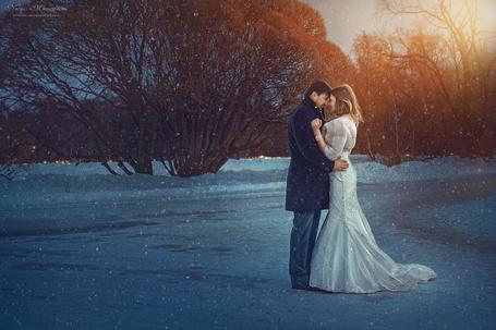 Фото Девушка в свадебном платье и ее жених стоят в обнимку на дороге под падающим снегом, фотограф Дмитрий Плотников