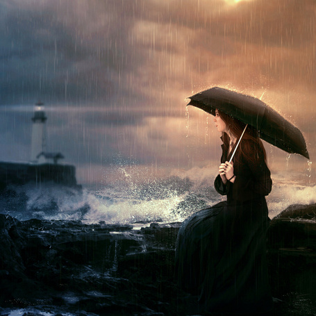 Фото Девушка с черным зонтом сидит у моря, позади виднеется маяк