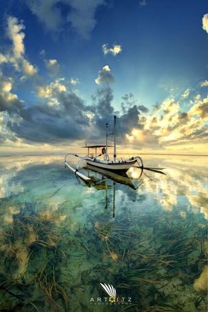 Фото Необычная лодка посреди водоема с прозрачной водой, где отражаются облака