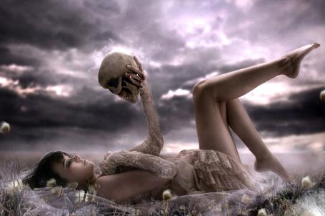 Фото Девушка с черепом в руке лежит в траве