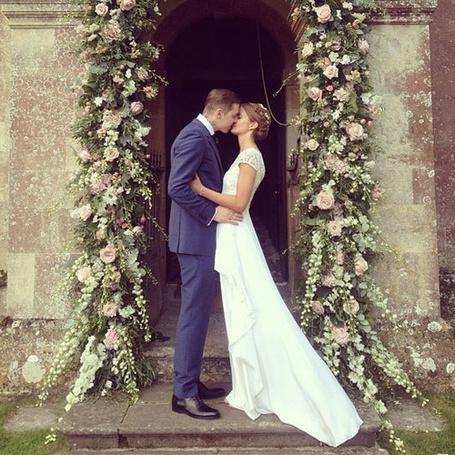 Фото Жених и невеста целуются возле украшенного цветами входа в церковь