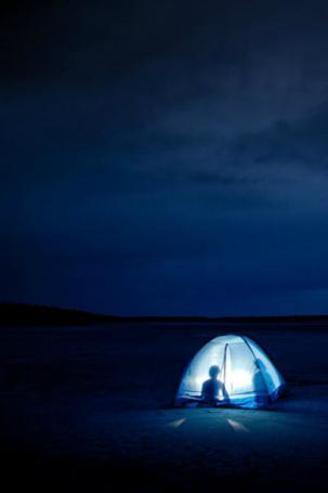 Фото Двое мужчин сидят в палатке на фоне ночного неба