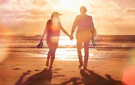 Фото Влюбленные идут к морю, держась за руки, парень несет бутылку шампанского, а девушка свои босоножки