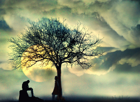 Фото Парень сидит на камне, а девушка стоит у дерева