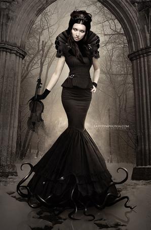Фото Девушка стоит со скрипкой в руке, позади арка и деревья