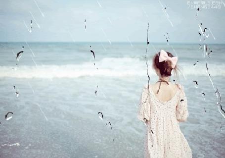 Фото Девушка у моря, вид через стекло, по которому стекают капли дождя