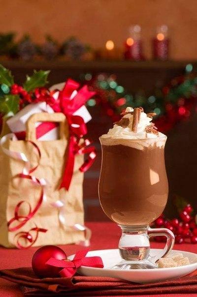 Фото Бокал горячего шоколада со взбитыми сливками, корицей и шоколадом, стоит на тарелке, на фоне елочных украшений и новогодних подарков