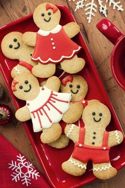 Фото Новогодние печенье в виде радостных человечков, одетых в цветастые платья и штанишки, лежит на красной тарелке