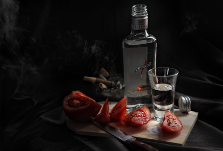 Фото Бутылка водки с рюмкой, рядом лежат помидоры,