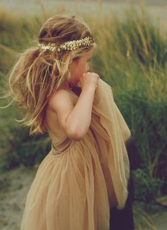 Фото Девочка в бронзовом платье и с венком на голове стоит в глубокой траве