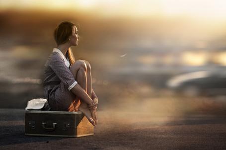 Фото Мечтательная девушка сидит на чемодане поджав ноги на улице. Фотограф Елена Шумилова / Elena Shumilova