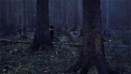 Фото Черные монстры выглядывают из-за деревьев в лесу, один из них резко появляется впереди