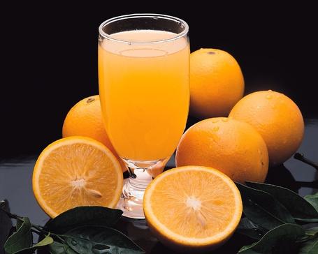 Фото Стакан апельсинового сока стоит рядом с плодами апельсина