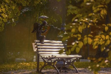 Фото Скамейка в осеннем парке с сидящей на ее спинке фигуркой ангела