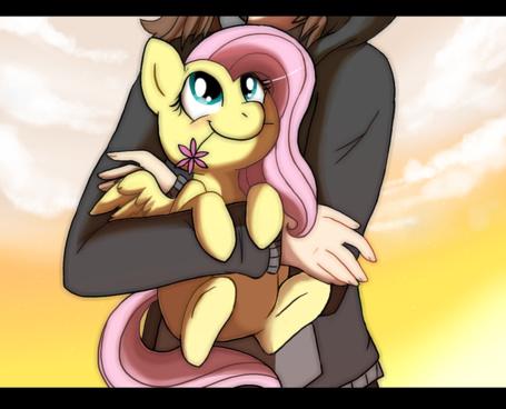 Фото Маленькая Флатти / Flutty / Флаттершай / Fluttershy с розовым цветочком на руках у девочки в серой куртке, art / арт по мотивам мультсериала Мой маленький пони: Дружба - это чудо / My Little Pony: Friendship is Magic / MLP:FiM