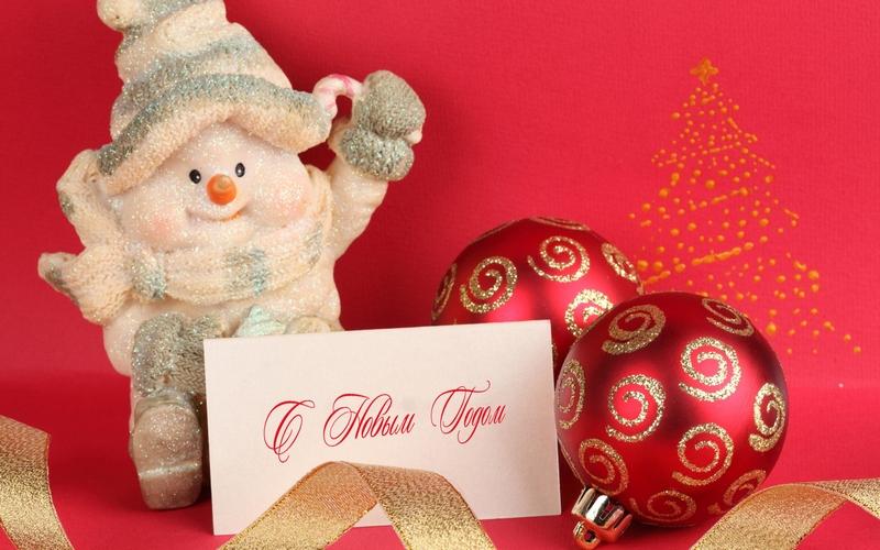 Фото Новогодний снеговик сидит рядом с красными шарами и в ногах у него бумага с надписью С Новым Годом