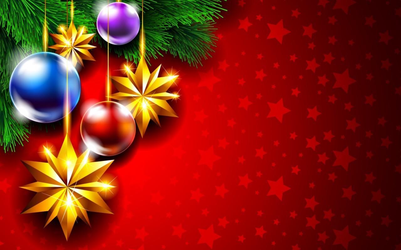 Фото Еловая ветка с новогодними игрушками на красном фоне