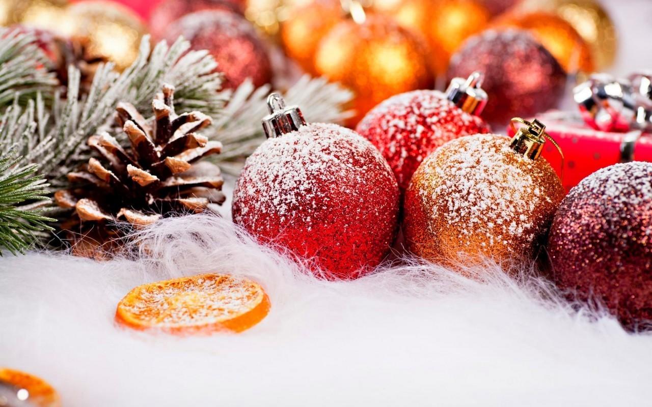 Красные новогодние шары лежат у сосновой ветки с шишками