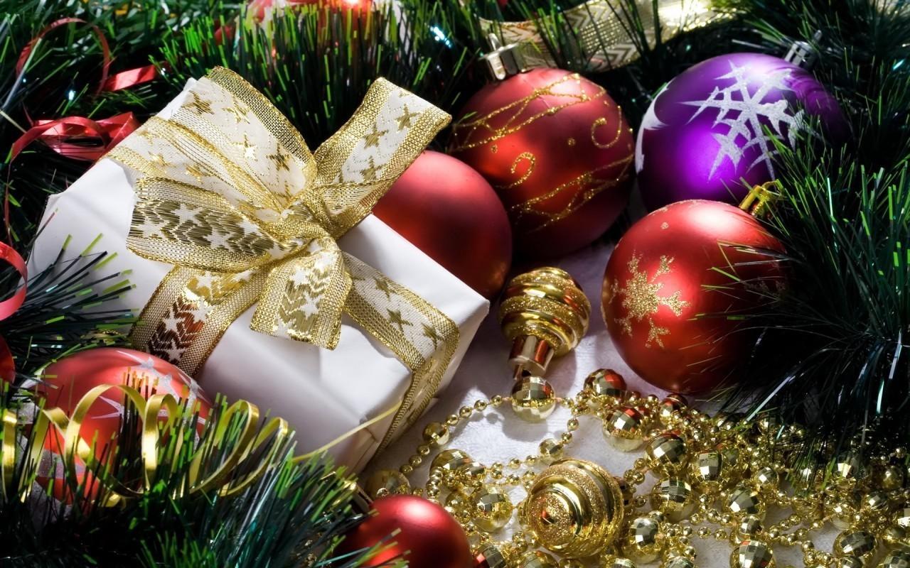Синий и красные новогодние шарики с подарком лежат на белой материи