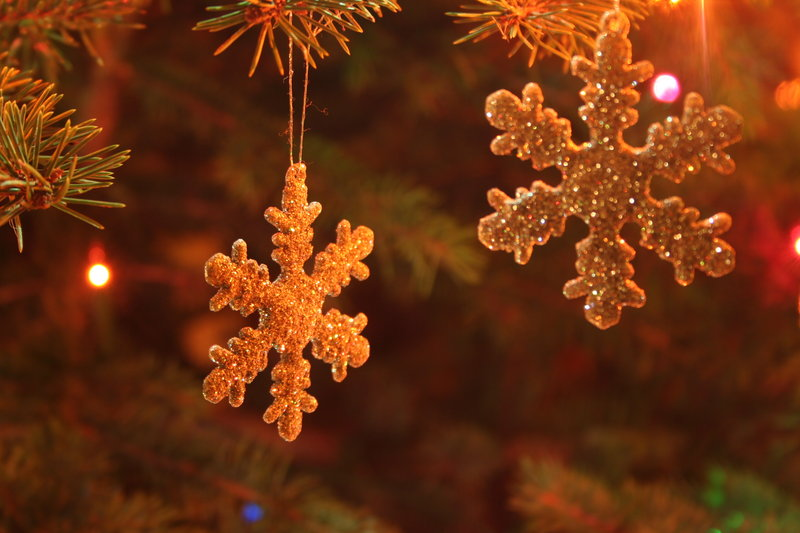 Фото Две игрушечные снежинки висят на елке