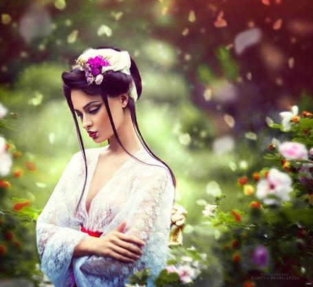 Фото Девушка в белой кофточке сложила руки у груди стоя на фоне летающих лепестков цветов, фотограф Margarita Kareva