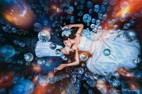 Фото Жених и невеста лежат на полу целуясь среди множества мыльных пузырей, фотограф Наталья Макушева