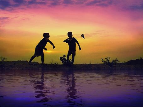 Фото Два мальчик запускают бумажный самолет, стоя на берегу водоема на фоне закатного неба, фотограф Tri Joko