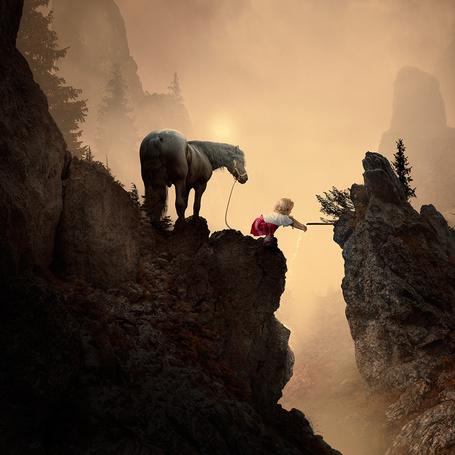 Фото Маленькая, белокурая девочка в белой блузке и красной юбке моет руку под водой, текущей из металлической трубы, стоящей в расщелине скалы, рядом с девочкой стоит конь, на фоне неба в туманной мгле с едва заметным солнечным диском, автор Garas Ionut