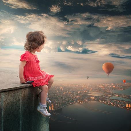 Фото Маленькая девочка, сидящая на крыше здания с птичьим перышком в руках наблюдает за полетом воздушных шаров в небе над городом, автор Garas Iount