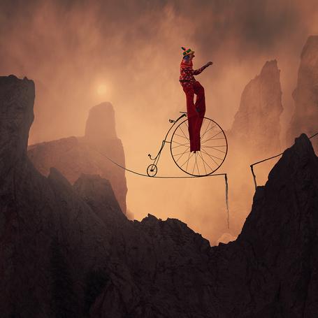 Фото Цирковой клоун на двухколесном велосипеде пытается проехать по канату, натянутому между пиками горной вершины, автор Garas Iount
