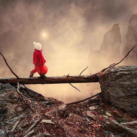 Фото Маленькая девочка в красном пальто и белой вязанной шапочке, идущая по бревну, лежащему между каменными валунами в горах, держа в руке надувной красный шарик, автор Garas Iount