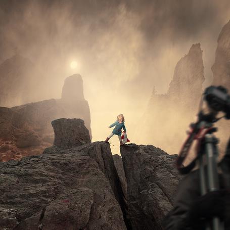 Фото Маленькая девочка, держащая в руках мягкую игрушку, стоит над расщелиной в горах, автор Garas Iount