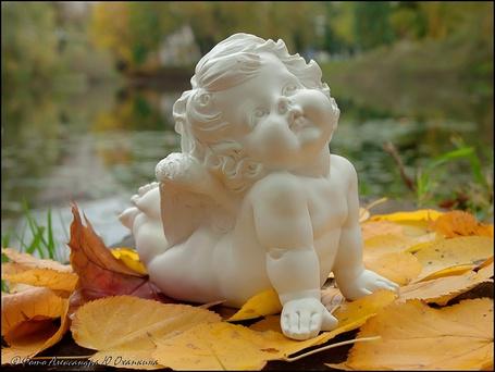 Фото Скульптура девочки - ангела, которая лежит на осенних листьях, фотограф А. Ю. Охапкин