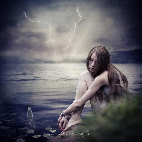 Фото Босоногая, длинноволосая, грустная девушка, сидящая на берегу моря на фоне грозового неба и разрядов молнии, рядом с берегом плавает закупоренная стеклянная бутылка с посланием внутри, автор Blood-Fridge