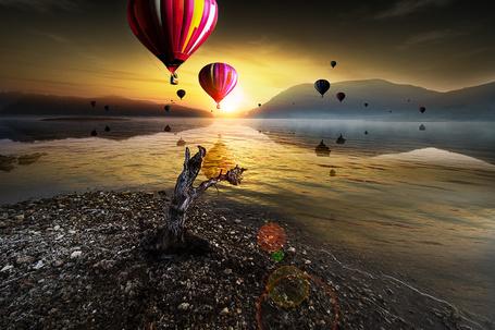 Фото Разноцветные воздушные шары, парящие над горным озером в потоках солнечных лучей восходящего солнца