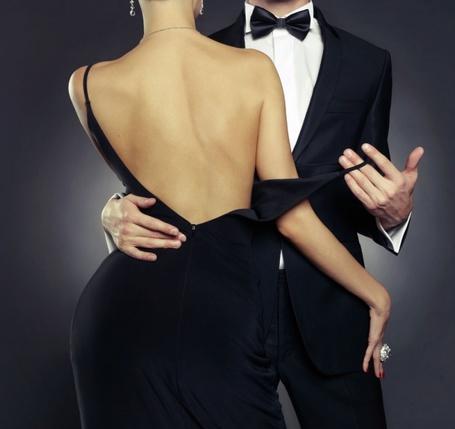 Фото Парень держит бретельку платья девушки, стоящей к нам спиной в черном платье с оголенной спиной