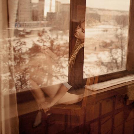 Фото Девушка сидит у окна, за которым видна городская улица с домами, работа одиночество, фотограф Сергей Филимонов